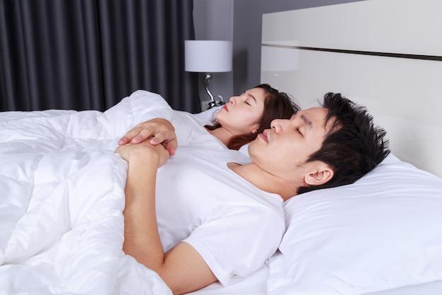 Casal dormindo em uma cama confortável no quarto em casa