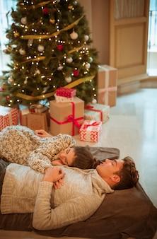 Casal dormindo na árvore de natal