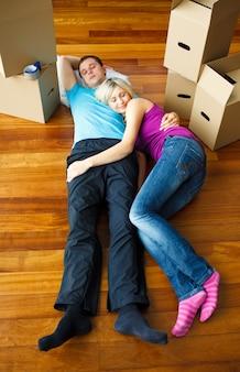 Casal dormindo no chão. mudança de casa