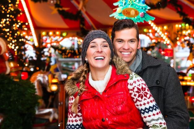 Casal durante o mercado de natal ou temporada de advento