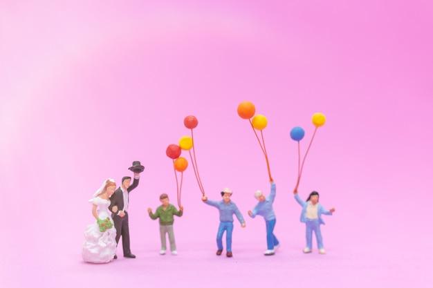 Casal e família com balões coloridos comemorando
