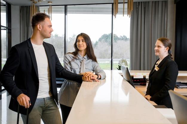 Casal e recepcionista no balcão do hotel. jovem casal em viagem de negócios fazendo check-in no hotel