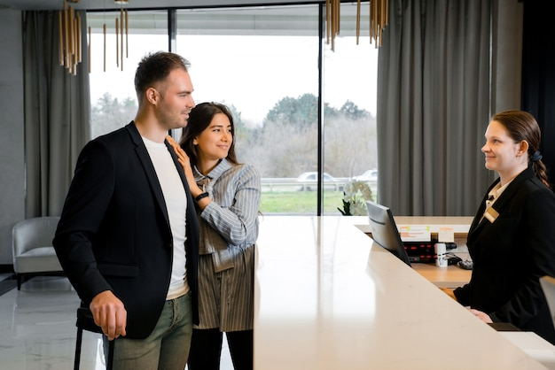 Casal e recepcionista no balcão do hotel. jovem casal fazendo check-in no hotel
