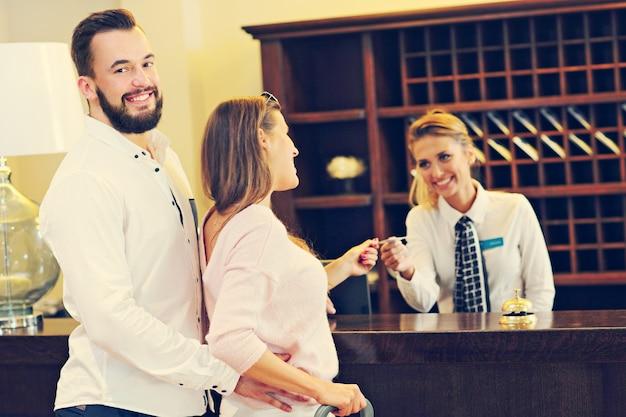 Casal e recepcionista no balcão do hotel