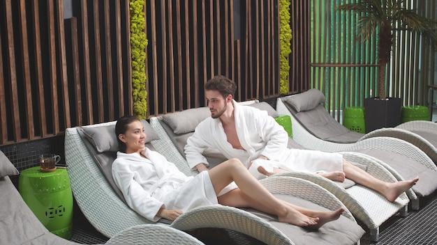 Casal é relaxante no centro de spa. uma mulher e um homem cuidam de sua saúde