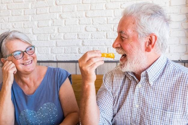 Casal e retrato de dois idosos maduros felizes comendo em um fast food ou restaurante juntos, sorrindo e se divertindo, rindo - estilo de vida feliz e fofo e o conceito de dois aposentados em casa