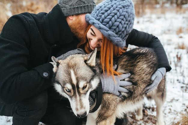 Casal e um cachorro fora da cidade