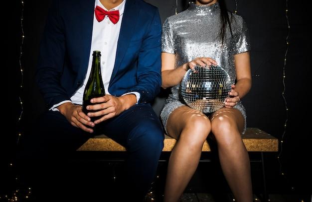 Casal elegante com bola de discoteca e garrafa de champanhe