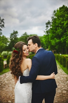 Casal elegante de recém-casados felizes posando no parque no dia do casamento. casal perfeito, noiva e noivo posando e se beijando