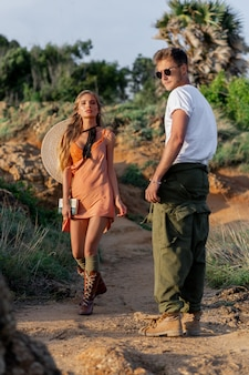Casal elegante descoladosa jovem em uma camiseta branca, óculos e calças largas, uma garota em um vestido largo, botas casuais e um chapéu nas costas. estilo boho ao ar livre