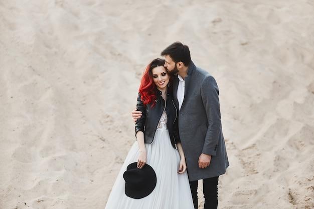 Casal elegante e elegante, garota modelo sexy com cabelo vermelho e maquiagem brilhante, vestido de renda e elegante jaqueta de couro e homens barbudos bonitos com casaco cinza na moda, posando no deserto