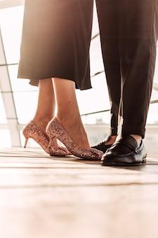 Casal elegante em frente à luz do sol no chão de madeira perto de grades