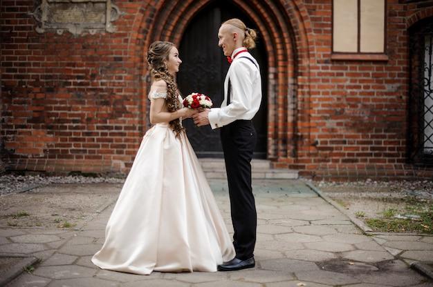 Casal elegante em pé e sorrindo no fundo do arco de um prédio de tijolos vermelhos