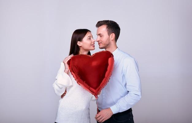 Casal elegante em um fundo cinza com um coração vermelho.