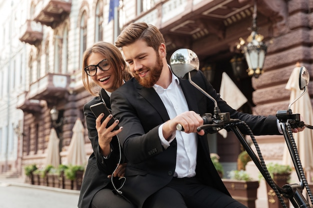 Casal elegante feliz sentado na moto moderna ao ar livre