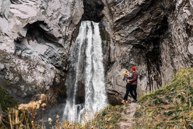 Casal elegante na cachoeira. um homem e uma mulher viajando no cáucaso. um casal apaixonado está viajando pela rússia. casal de turistas elegantemente vestidos ao pé de uma grande cachoeira. copie o espaço