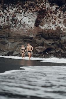 Casal elegante na praia perto de pedras