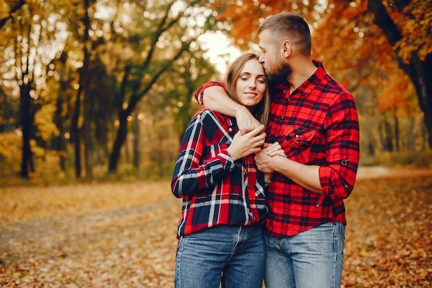 Casal elegante passar o tempo em um parque de outono
