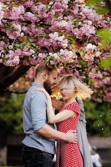 Casal elegante perto da árvore de sakura