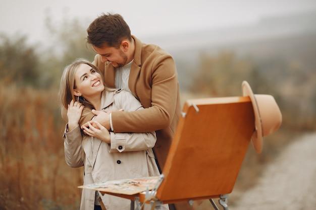 Casal elegante pintura em um campo de outono
