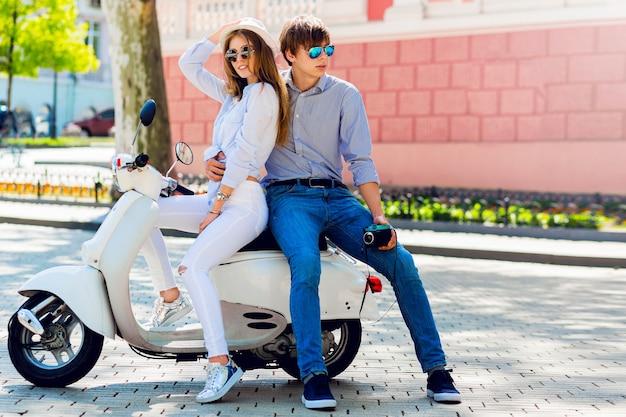 Casal elegante posando na rua, sentado em uma scooter
