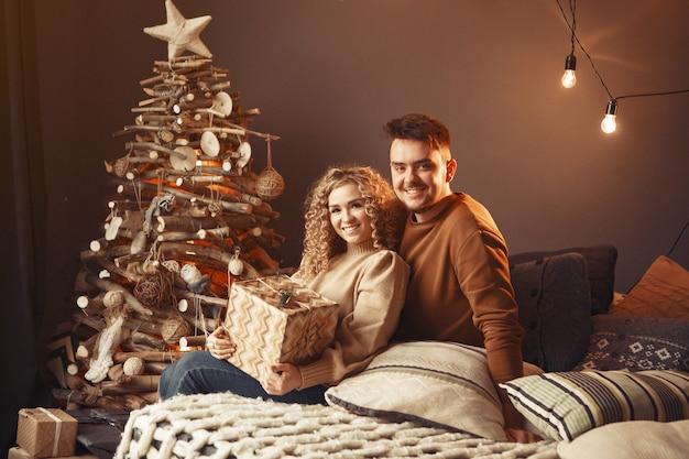 Casal elegante sentado em casa perto da árvore de natal