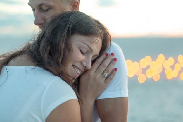 Casal em abraços românticos de amor no deserto de areia. noite, atmosfera romântica, na areia queimar velas