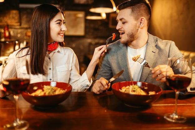 Casal em balcão de bar de madeira, jantar romântico