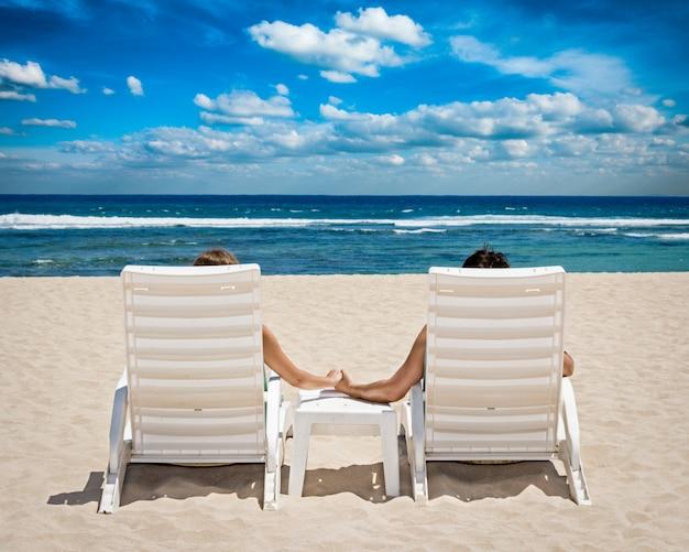 Casal em cadeiras de praia, segurando as mãos perto do oceano