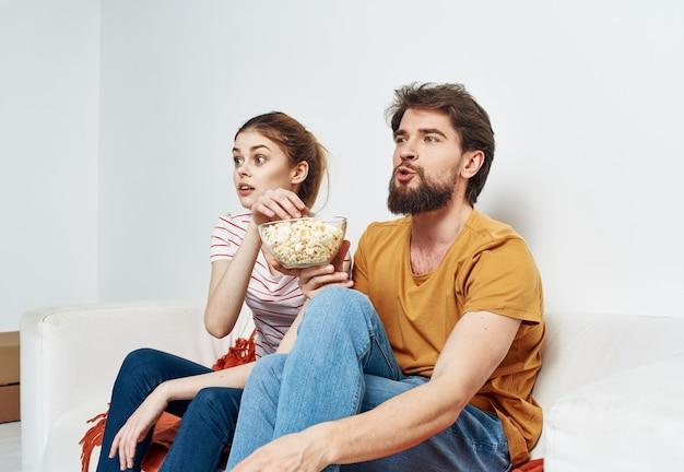 Casal em casa assistindo filme e comendo pipoca