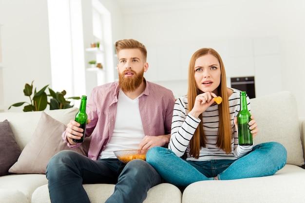 Casal em casa assistindo tv juntos e tomando cerveja