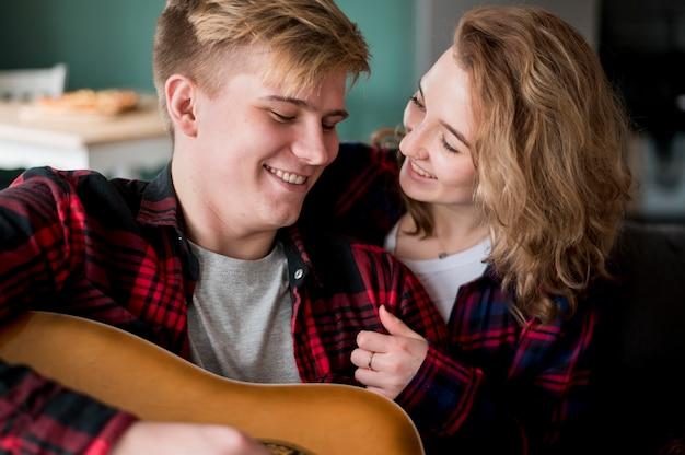 Casal em casa com guitarra