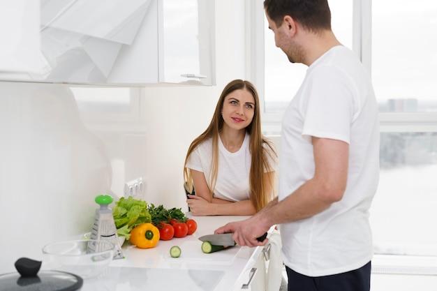 Casal em casa fazendo salada