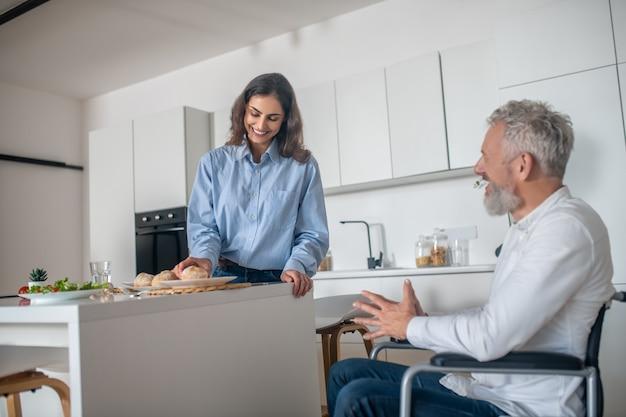 Casal em casa. jovem mulher fazendo café da manhã, seu marido deficiente sentado perto
