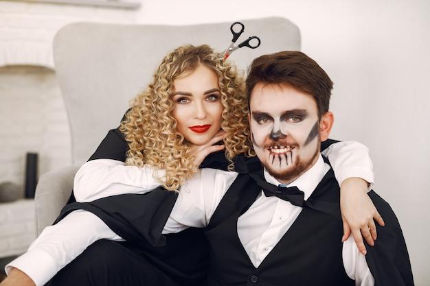 Casal em casa. mulher vestindo fantasia preta. senhora com maquiagem de halloween.