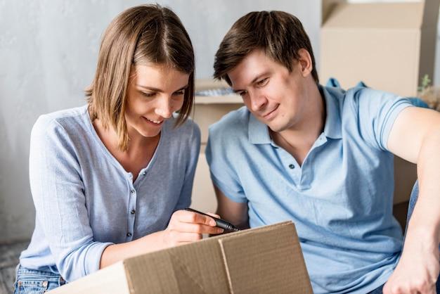 Casal em casa no dia da mudança caixa de rotulagem