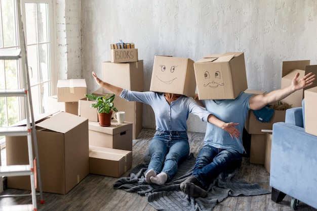Casal em casa no dia da mudança com caixas sobre as cabeças