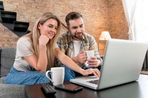 Casal em casa tendo videochamada com a família