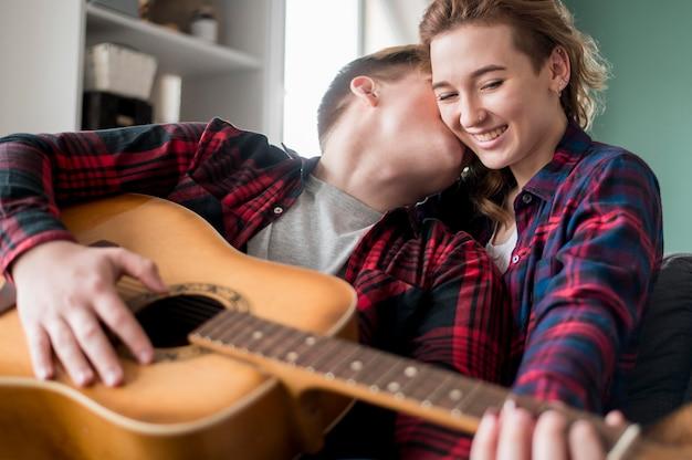 Casal em casa tocando violão
