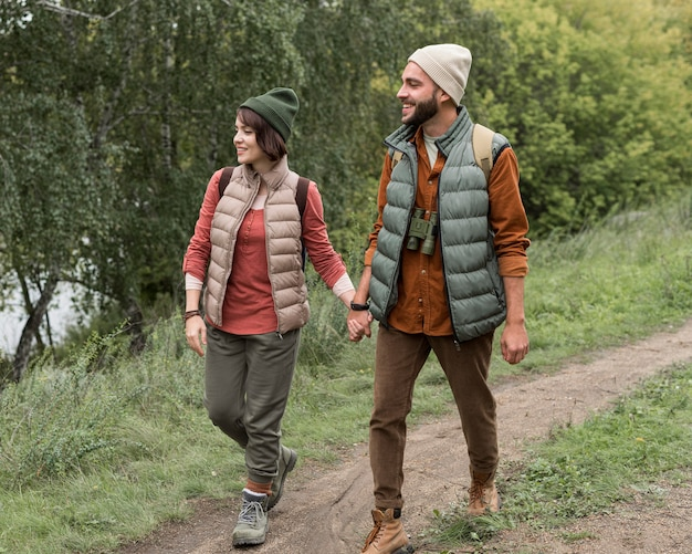 Casal em cena completa caminhando em uma trilha na natureza