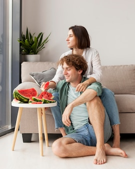 Casal em cena completa comendo melancia