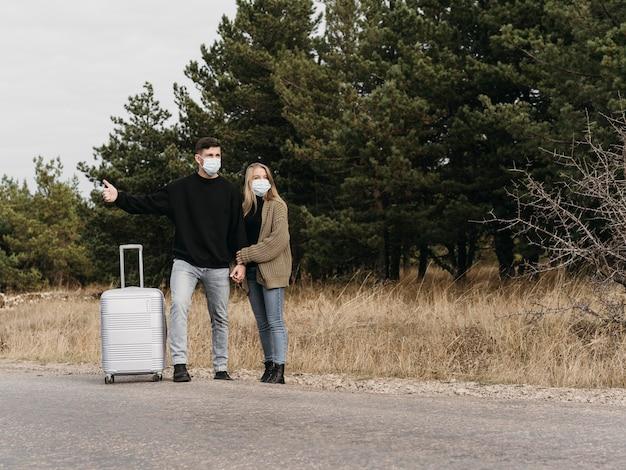 Casal em cena completa pedindo carona com a bagagem