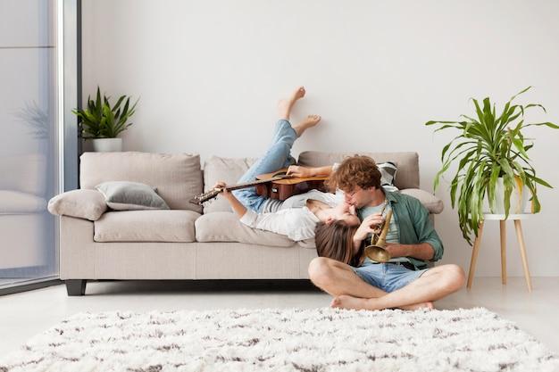 Casal em cena completa se beijando na sala de estar