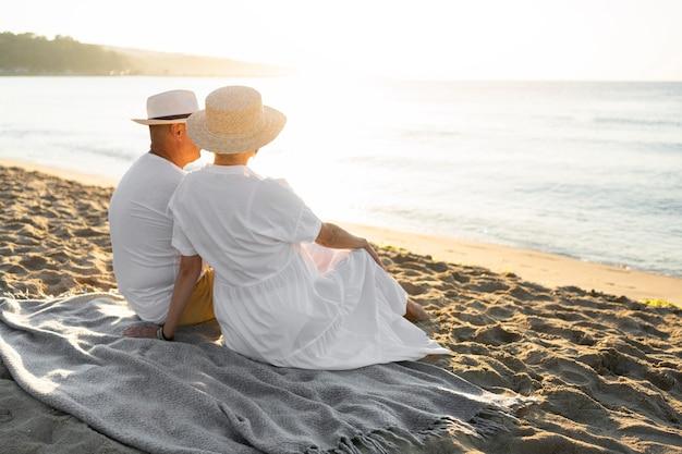 Casal em cena completa sentado no cobertor