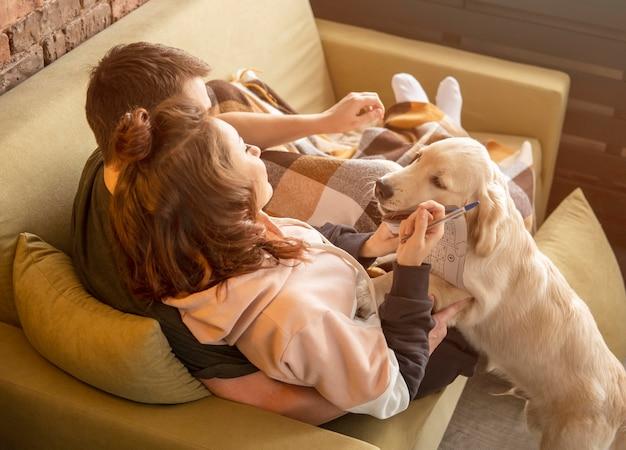 Casal em cena no sofá com cachorro