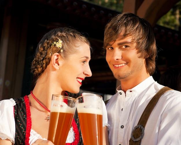 Casal em cerveja de trigo bebendo bávaro tracht