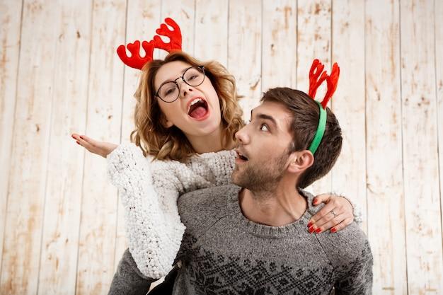 Casal em chifres de veado falso posando se divertir ao longo da parede de madeira