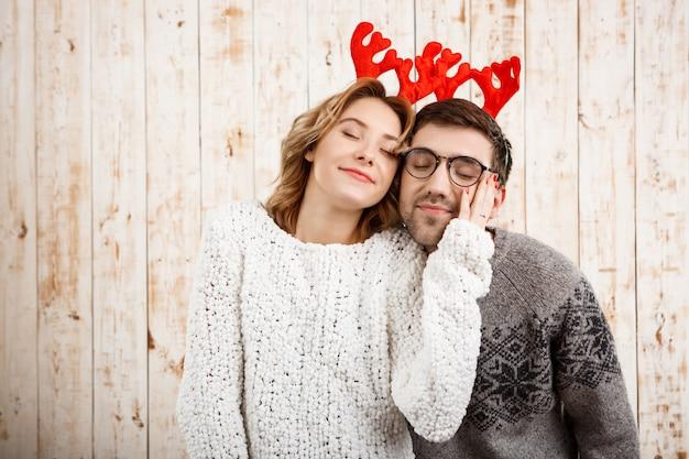 Casal em chifres de veado falso sorrindo sobre parede de madeira