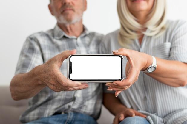 Casal em close segurando smartphone