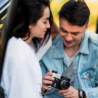 Casal em close usando uma câmera retro